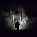 officer facing away from us walking through the woods at night holding a flashlight