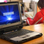 Panasonic Toughbook sitting on desk with person in the background