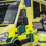 Medic holding Panasonic FZ-A2 Toughpad to the right of a yellow and green ambulance